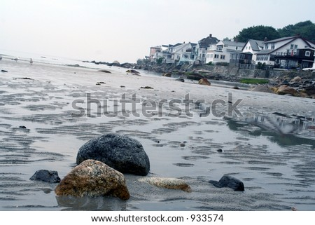 sand and stones on the beach near a costal town - stock photo