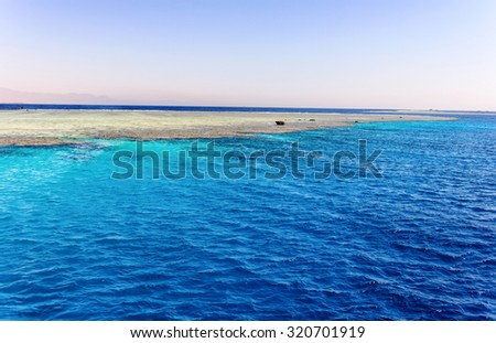 Sand bank mid ocean exposed by the receding water at low tide on a sunny summer day conceptual of a tropical vacation - stock photo
