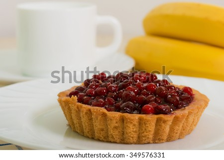 Sand basket with cranberries on white plate and banana - stock photo