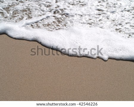 sand beach and foamy water. - stock photo