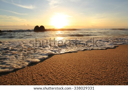 Sand beach and wave on sunrise,Solf focus because of slow shutter speed - stock photo