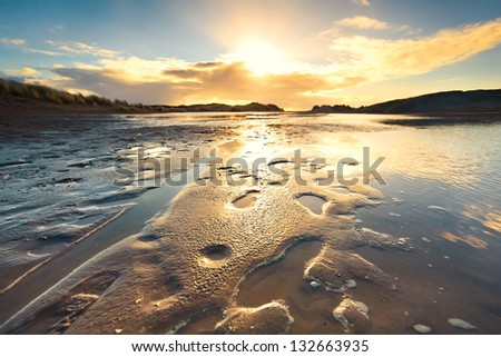 sand beach by North sea at low tide during sunset - stock photo