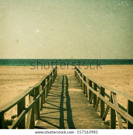Sand beach of Tarifa, Andalusia in grunge and retro style. Pier on the foreground