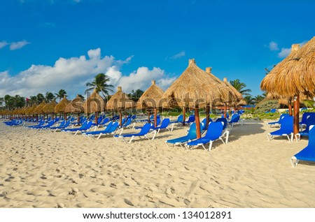 Sand beach with some grass umbrellas at the luxury caribbean resort.