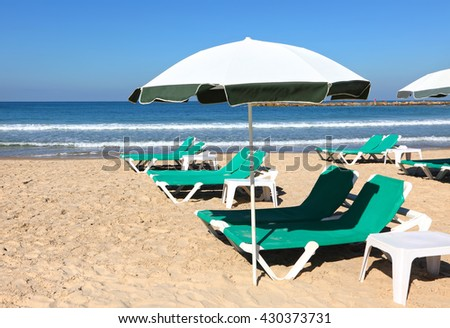 Sand beach with sun umbrella and green lounges. Summertime or vacation theme - stock photo