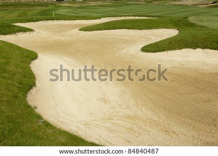 sand bunker on  a beautiful golf course - stock photo