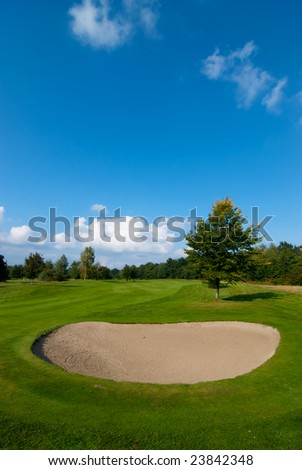 sand bunker on golf course with green grass and blue sky