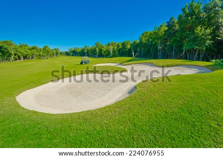 Sand bunker on the beautiful golf course with the golf cart at the back. Mexican resort. - stock photo