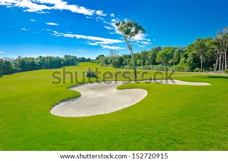 Sand bunker on the beautiful golf course with the golf cart at the back. Mexican resort. Bahia Principe.  Riviera Maya. - stock photo