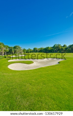 Sand bunker on the golf course. Mexican resort. Bahia Principe, Riviera Maya. Vertical. - stock photo
