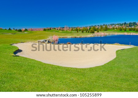 Sand bunker on the golf course with the pond and dark blue sky. - stock photo