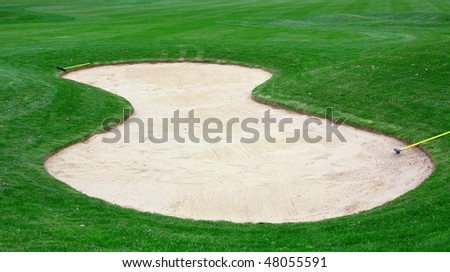 Sand bunker on the green grass - stock photo