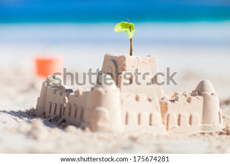 Sand castle and beach toys at tropical coast - stock photo