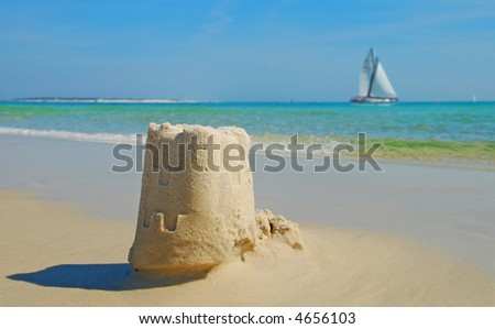 Sand Castle and Sailboat - stock photo