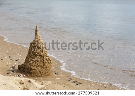 Sand castle, destroyed by the surf. Black Sea coast. Space for text. - stock photo