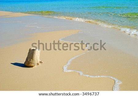 Sand Castle Escaping Waves - stock photo
