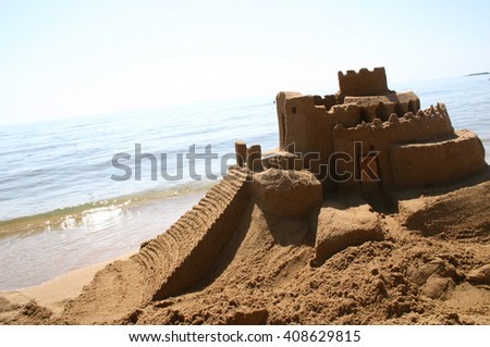 Sand castle from aside on beautiful beach - stock photo