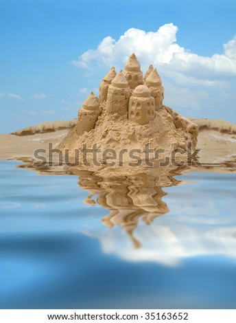 Sand castle on blue sky background with reflection on water - stock photo