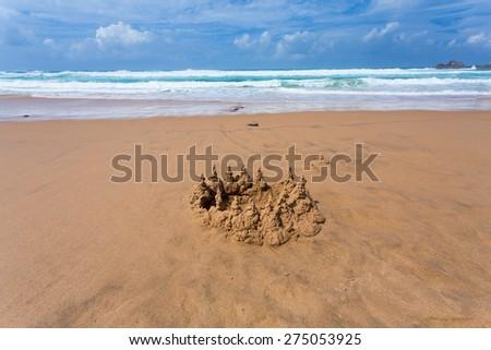 sand castle on the beach of the ocean - stock photo