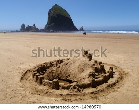 Sand castle on the ocean beach - Cannon Beach, Oregon - Haystack Rock in background - stock photo