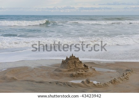 Sand castle surrounded by a moat on the beach.  Ocean and cloud filled sky in the background. - stock photo