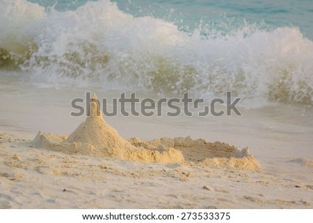Sand castle tower and strong waves - stock photo