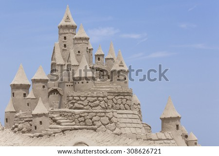 Sand Castle with blue background. Copy space  - stock photo