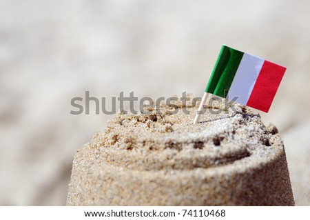 Sand castle with Italian flag - stock photo
