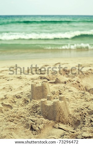 sand castle with ocean - stock photo