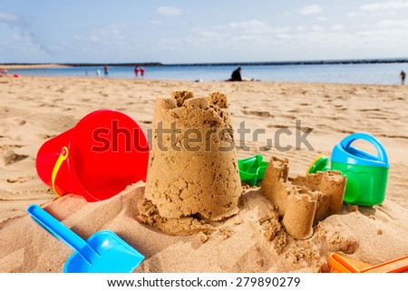 sand castle  with plastic toys on the sunny summer  beach  - stock photo