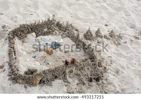 Sand castle with stones and mussel shells