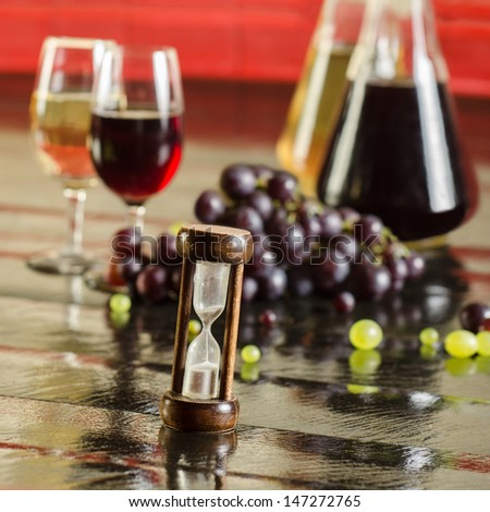 Sand clock, grapes, wine bottles and wine glasses - stock photo