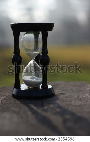 sand clock showing how is time passing, laid on a wood stump - stock photo