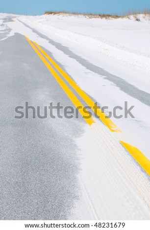Sand covering washed out highway after storm surge - stock photo