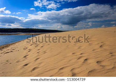 Sand dune and clouds on blue sky by Chancza lake, Poland