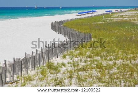 Sand dune fence and grasses at beautiful resort beach - stock photo