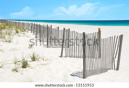 Sand dune fence and grasses at pretty beach - stock photo