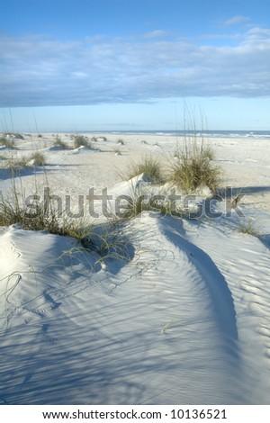 Sand Dune ripples near ocean with blue sky - stock photo