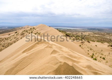 sand dune with bushes on a background of mountains - stock photo