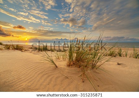 Sand dunes against the sunset light on the beach in northern Poland - stock photo