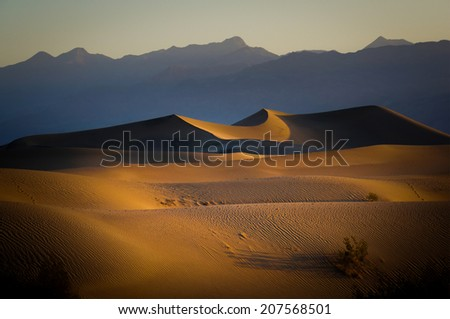 Sand Dunes And Mountains in sunrise, Death Valley National Park, California, USA - stock photo