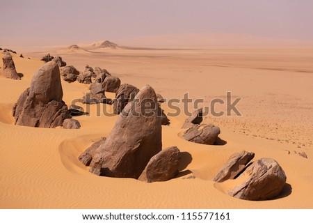 Sand dunes and stones in the Sahara desert - stock photo