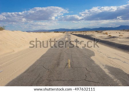 Sand dunes blow across abandoned desert road in the Mojave wilderness.