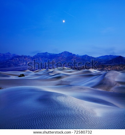 Sand Dunes, Mountains And Moonrise In The Predawn Light At Stovepipe Wells, Death Valley National Park, California, USA - stock photo