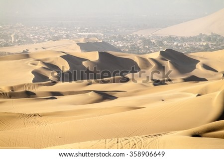 Sand dunes near Huacachina, Peru. Ica city in the background. - stock photo