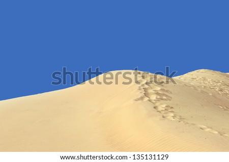 Sand dunes on the blue sky background - stock photo