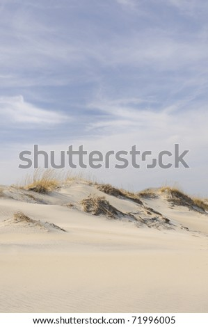 Sand dunes on windy day - stock photo