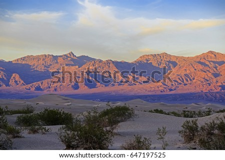 Sand dunes red cliffs near Death Valley at sunset, California, USA