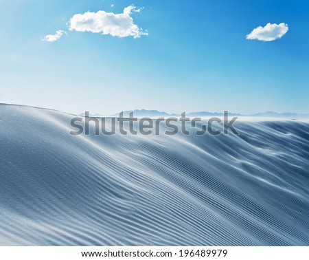 Sand dunes under a blue sky with three small clouds. - stock photo