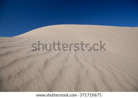 Sand dunes with a blue sky. Royla Dunes near Yuma, Arizona - stock photo
